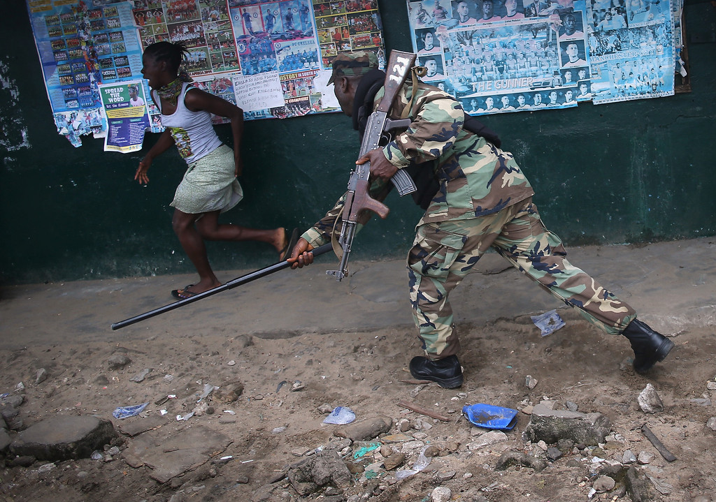 . MONROVIA, LIBERIA - AUGUST 20:  A Liberian Army soldier, part of the Ebola Task Force, beats a local resident while enforcing a quarantine on the West Point slum on August 20, 2014 in Monrovia, Liberia. The government ordered the quarantine of West Point, a congested seaside slum of 75,000, on Wednesday, in an effort to stop the spread of the virus in the capital city. Liberian soldiers were also sent in to the seaside favela to extract West Point Commissioner Miata Flowers and her family members after residents blamed the government for setting up a holding center for suspected Ebola patients to be set up in their community. A mob overran and closed the facility on August 16. The military also began enforcing a quarrantine on West Point, a congested slum of 75,000, fearing a spread of the epidemic. The Ebola virus has killed more than 1,200 people in four African nations, more in Liberia than any other country.  (Photo by John Moore/Getty Images)