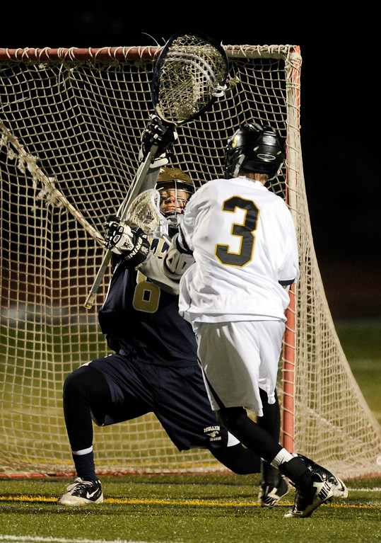 . LITTLETON, CO. - APRIL 10: Warriors senior attack Luc Crabtree (3) beat Mullen goalkeeper Jason Cleary (8) for a goal in the fourth quarter. The Mullen High School boy\'s lacrosse team defeated Arapahoe 8-7 Wednesday night, April 10, 2013. Photo By Karl Gehring/The Denver Post)