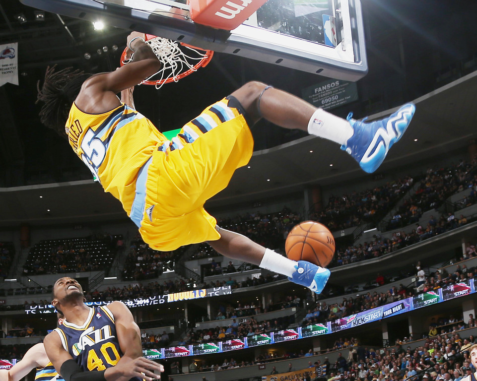 . Denver Nuggets forward Kenneth Faried, top, hangs on the rim after dunking the ball for a basket over Utah Jazz forward Jeremy Evans in the first quarter of an NBA basketball game in Denver on Saturday, April 12, 2014. (AP Photo/David Zalubowski)