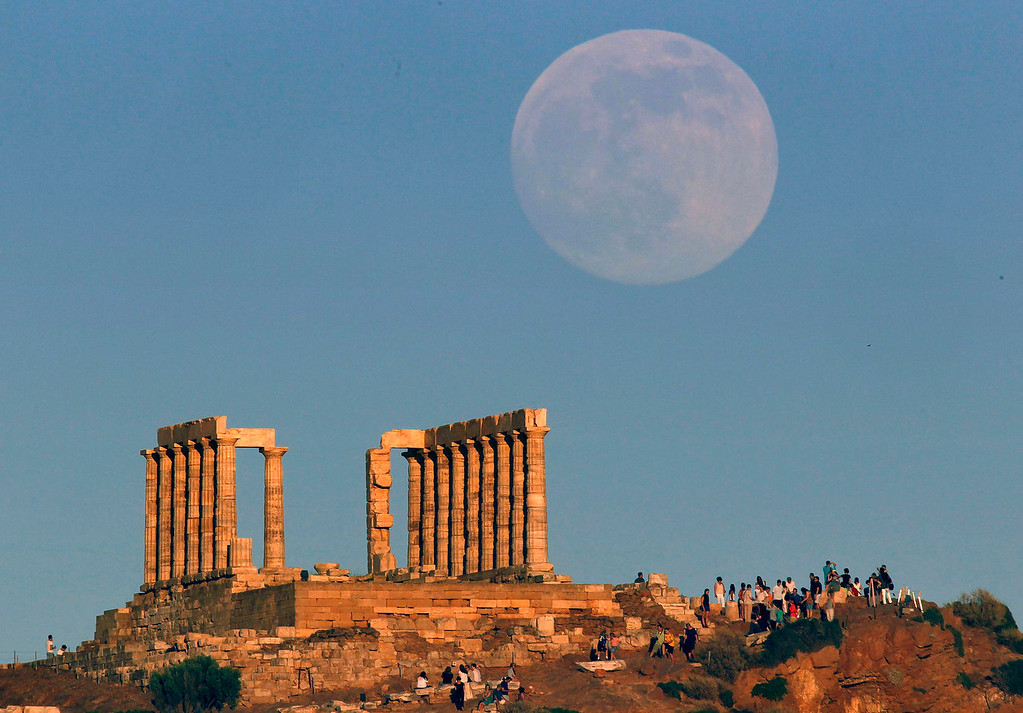 ". The moon rises over the temple of Poseidon, the ancient Greek god of the seas, as tourists enjoy the sunset in Cape Sounion some 60 km east of Athens on June 22, 2013. The moon will reach its full stage on Sunday and is expected to be 13.5 percent closer to earth during a phenomenon known as a ""super moon\"".  REUTERS/Yannis Behrakis"