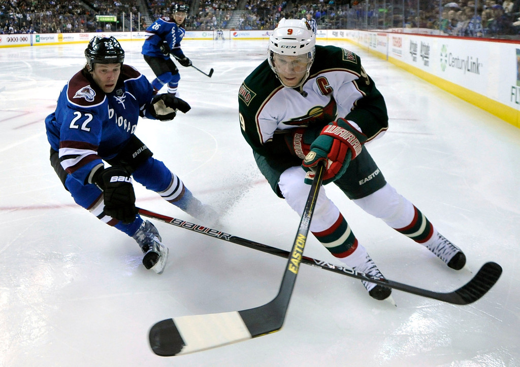 . Minnesota Wild center Mikko Koivu (9), from Finland, and Colorado Avalanche defenseman Matt Hunwick (22) chase the puck into the corner during the second period of an NHL hockey game on Saturday, March 16, 2013, in Denver. (AP Photo/Jack Dempsey)