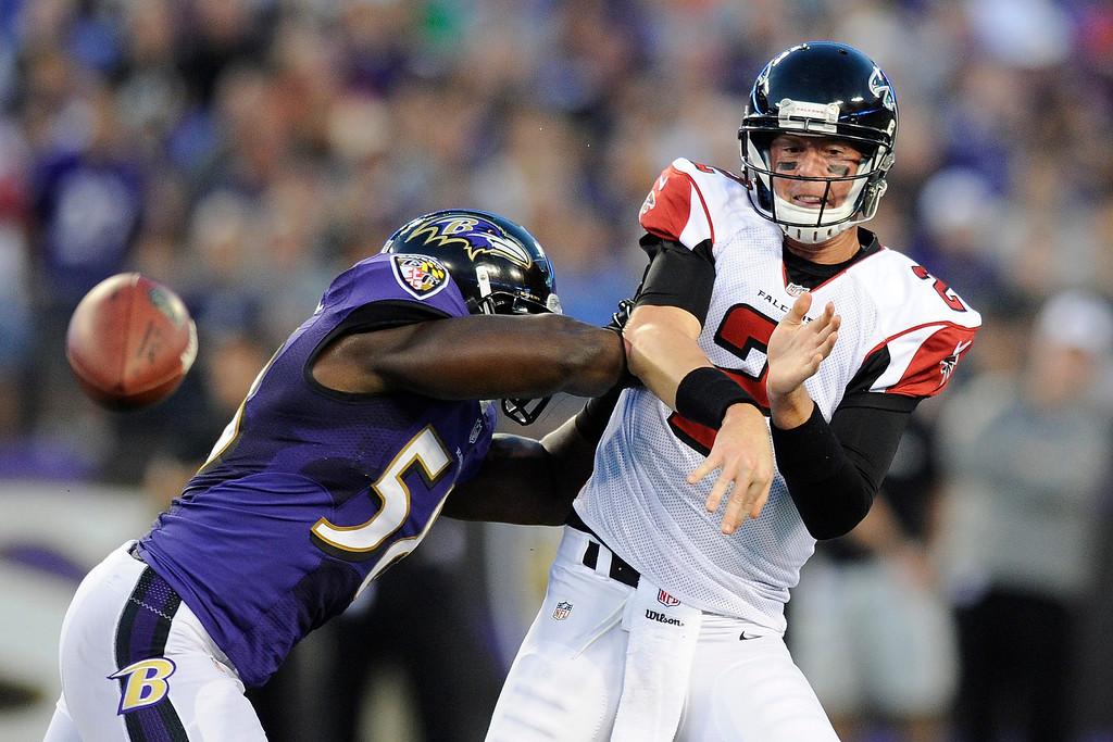 . Atlanta Falcons quarterback Matt Ryan releases a low pass under pressure from Baltimore Ravens linebacker Elvis Dumervil during the first half of a preseason NFL football game in Baltimore, Thursday Aug. 15, 2013. (AP Photo/Nick Wass)