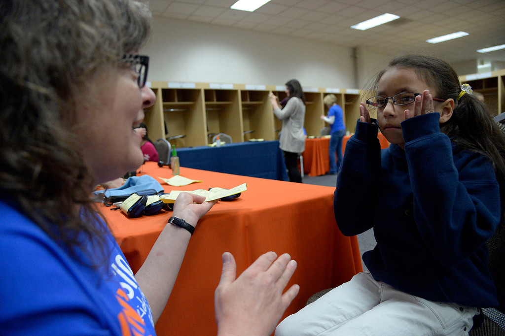 . Eileen Viapando fits Monsserat Jimenez Keria , 8, with her prescription glasses April 14, 2014. Miller\'s Foundation, Von\'sVision, distributed prescription glasses to more than 100 underprivileged children at Sports Authority Field. (Photo by John Leyba/The Denver Post)