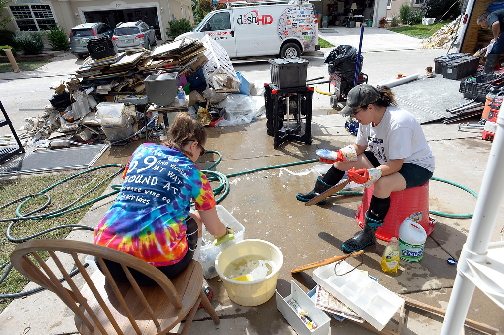 . Tiffany Brodie 38 years old (R) and Liza Gibbs 34 years old scrub items with soap and bleach 22, 2013 in the driveway surrounded by trash that was taken out of the basement damaged by the water. This house belongs to Tiffany\'s in-laws. (Photo by John Leyba/The Denver Post)