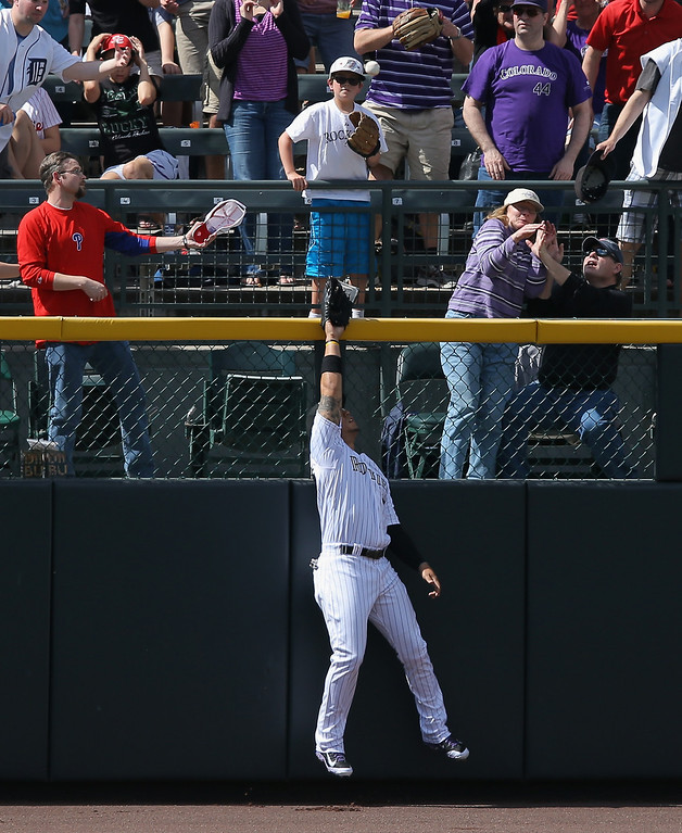 . Leftfielder Carlos Gonzalez #5 of the Colorado Rockies makes the attempt but catch reach the two run home run ball off the bat of Ryan Howard #6 of the Philadelphia Phillies in the third inning at Coors Field on April 20, 2014 in Denver, Colorado.  (Photo by Doug Pensinger/Getty Images)