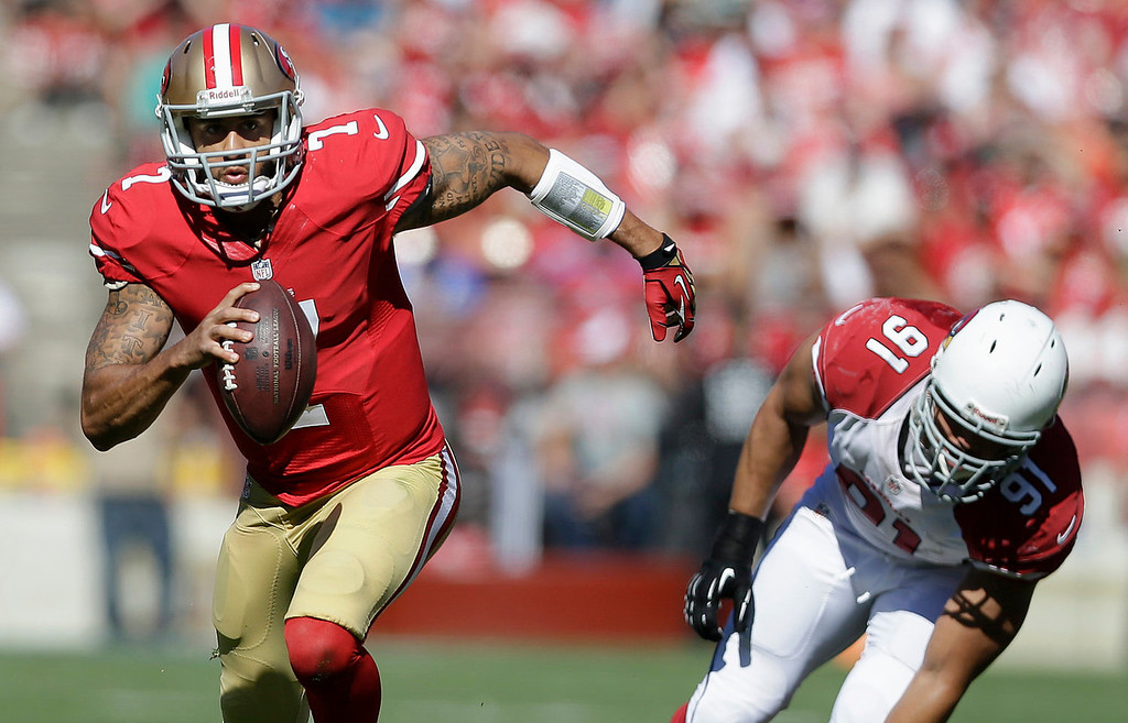 . San Francisco 49ers quarterback Colin Kaepernick (7) runs from Arizona Cardinals defensive end Matt Shaughnessy (91) during the second quarter of an NFL football game in San Francisco, Sunday, Oct. 13, 2013. (AP Photo/Marcio Jose Sanchez)
