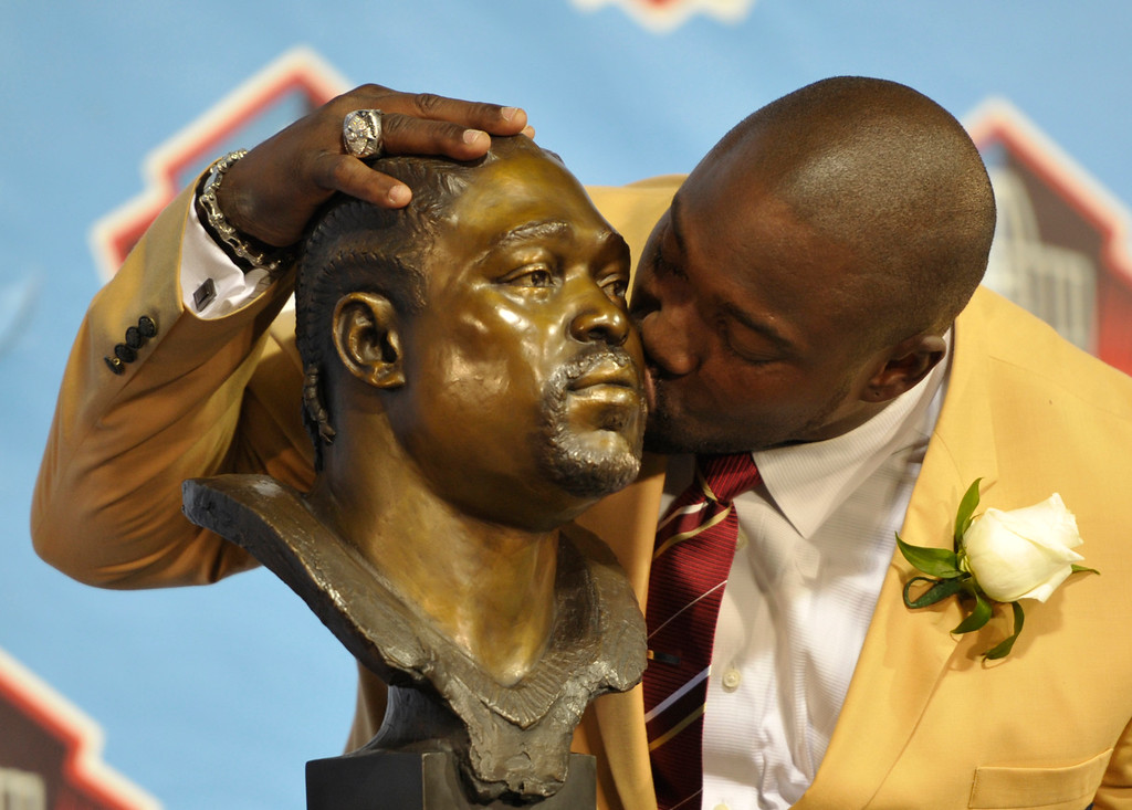 . Hall of Fame inductee Warren Sapp kisses his bust during the 2013 Pro Football Hall of Fame Induction Ceremony Saturday, Aug. 3, 2013, in Canton, Ohio. (AP Photo/David Richard)