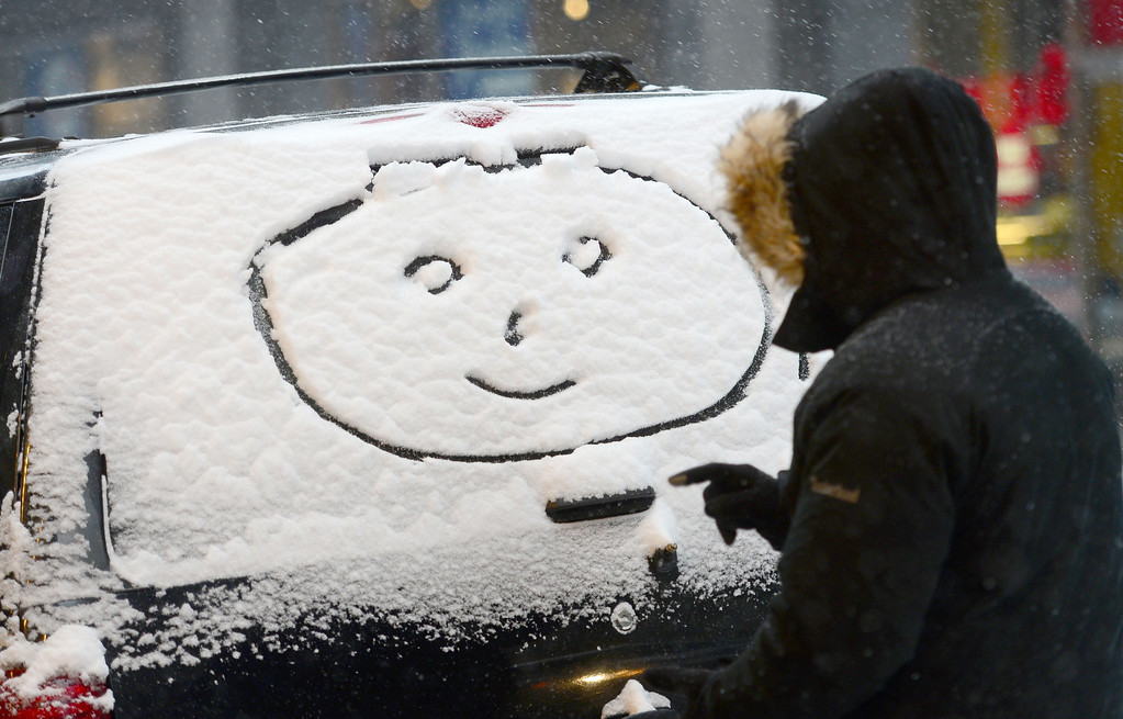 ". A person makes a ""happy face\"" on a car window during a snow storm in New York, January 22, 2014. AFP PHOTO/Emmanuel DUNAND/AFP/Getty Images"