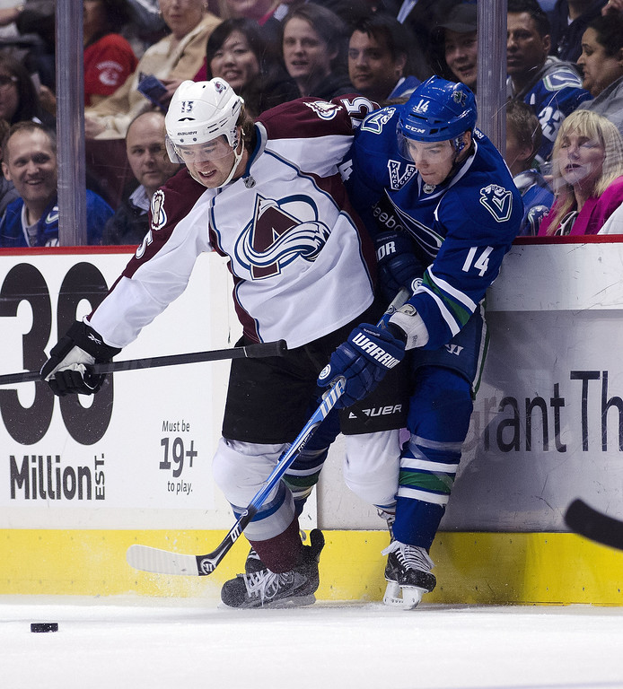 . PA Parenteau #15 of the Colorado Avalanche and Alexandre Burrows #14 of the Vancouver Canucks battle for the puck during the first period in NHL action on March 28, 2013 at Rogers Arena in Vancouver, British Columbia, Canada.  (Photo by Rich Lam/Getty Images)