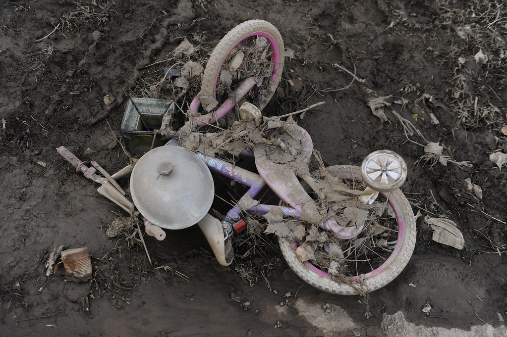. A child\'s bike is covered in dried mud inside the Eastwood Village mobile home park in Evans Saturday. Residents of Evans continued the grim work of salvaging personal belongings from flooded homes Saturday afternoon, September 21, 2013.  Photo By Karl Gehring/The Denver Post