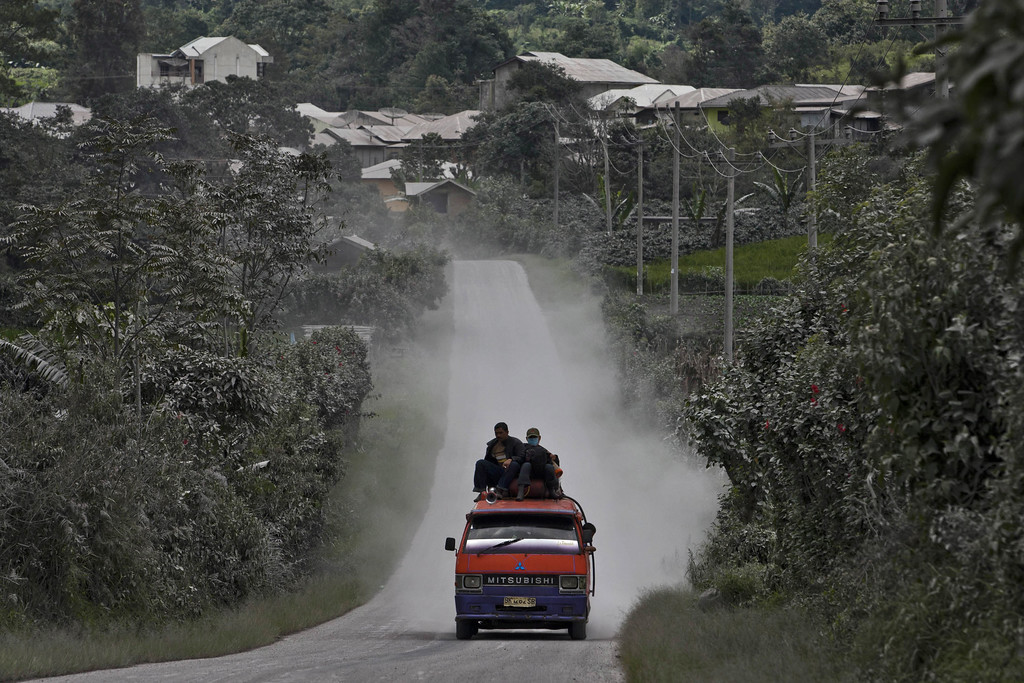 . A car passing through an area covered by ash after Mount Sinabung erupted spewing volcanic materials in Sigarang Garang village on November 25, 2013 in Karo district, North Sumatra, Indonesia. (Photo by Ulet Ifansasti/Getty Images)