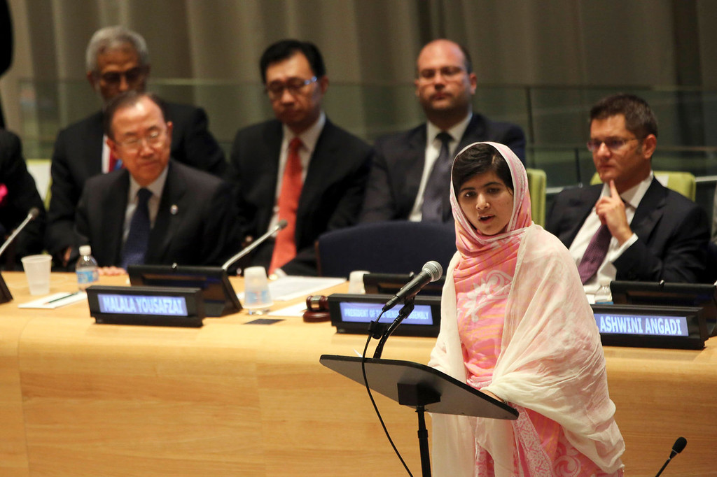 ". United Nations Secretary-General Ban Ki-moon, left, listens as  Malala Yousafzai, right, addresses the ""Malala Day\"" Youth Assembly, at United Nations headquarters on Friday, July 12, 2013. A year ago, Malala Yousafzai was a schoolgirl in northwest Pakistan. Today she\'s the world-famous survivor of a Taliban assassination attempt, an activist for girls\' education and a contender to win the Nobel Peace Prize on Friday Oct. 11, 2013. (AP Photo/Mary Altaffer, File)"
