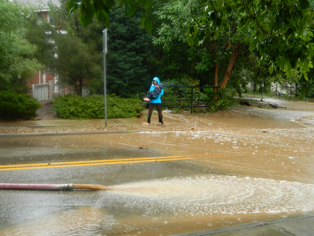 . A mother carries her daughter across a flooded Pearl St in Boulder. Photo by Jae Beaubier