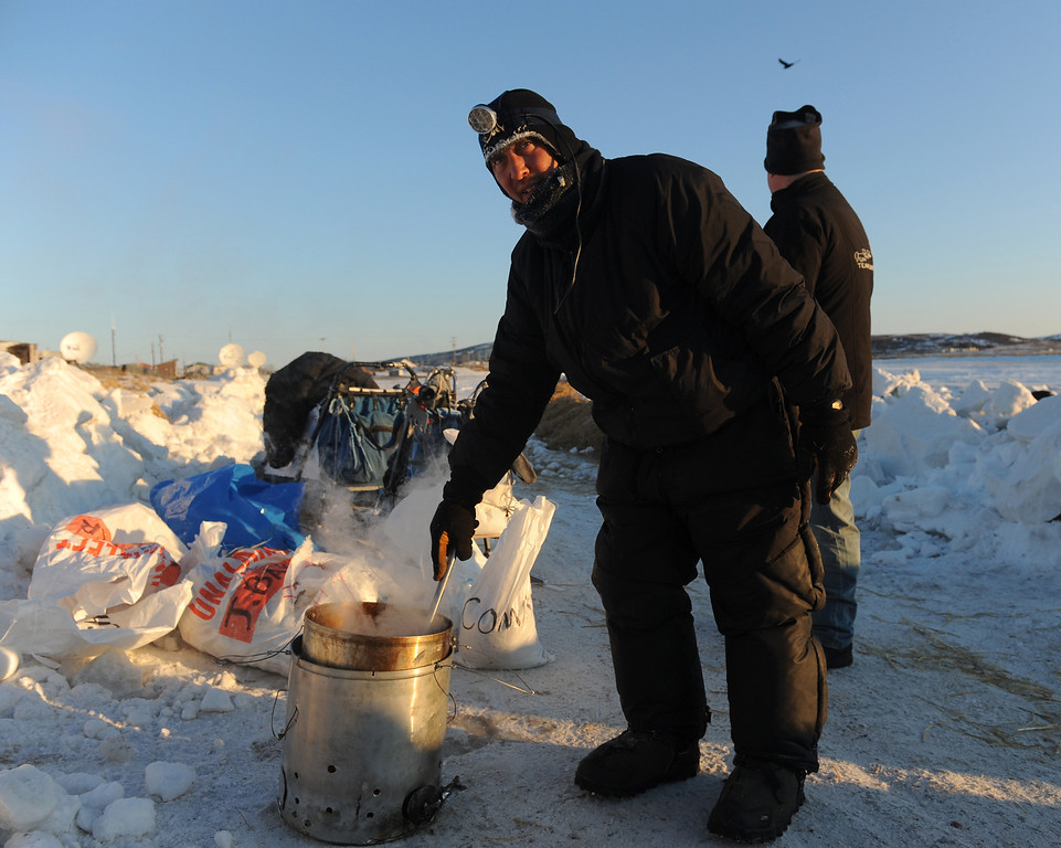 . Iditarod musher John Baker, from Kotzebue, Ak, prepares dog food for his team at the Unalakleet checkpoint at sunrise during the 2014 Iditarod Trail Sled Dog Race on Sunday, March 9, 2014. (AP Photo/The Anchorage Daily News, Bob Hallinen)
