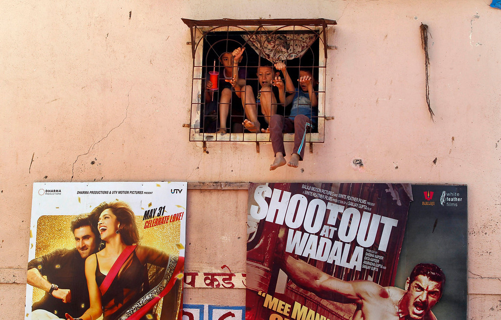 ". Children play behind a window of their house as Bollywood film posters are displayed on its wall in Mumbai, India, Friday, May 3, 2013. Four top Indian filmmakers have come together to make ""Bombay Talkies,\"" a short-film collection that hits theaters Friday to celebrate 100 years of Indian cinema. India\'s first full-length feature film \""Raja Harishchandra,\"" or \""King Harishchandra,\"" was released in 1913. Since then Indian cinema has become the largest producer of films in the world. India produced nearly 1,500 films last year, according to accounting firm KPMG. (AP Photo/Rajanish Kakade)"