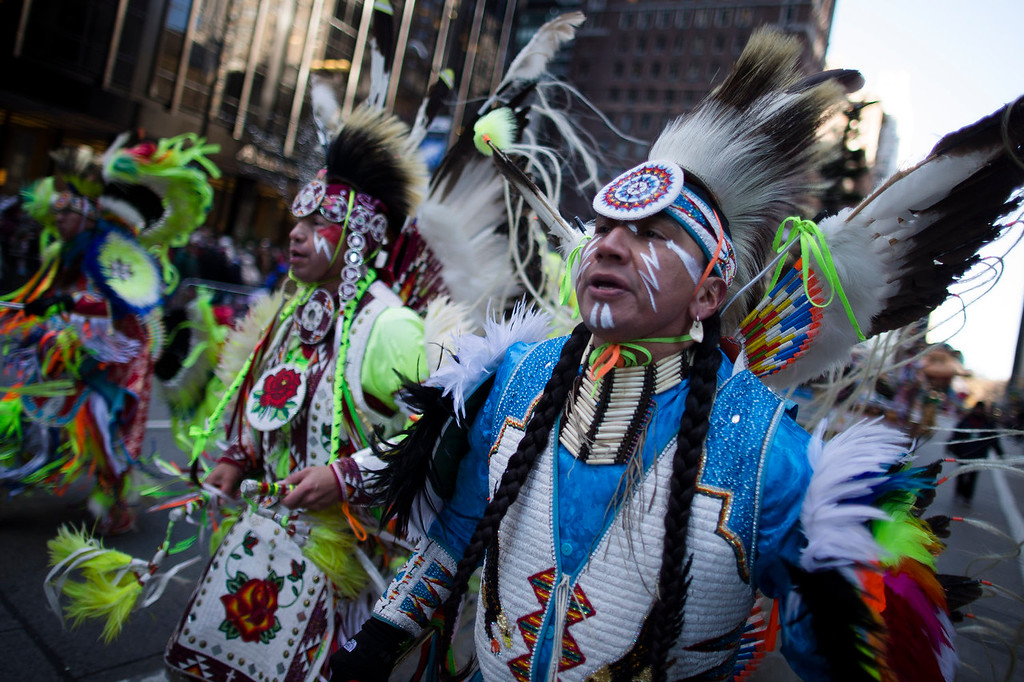 . A Native American performance group marches down 6th Avenue during the 87th Annual Macy\'s Thanksgiving Day Parade, Thursday, Nov. 28, 2013, in New York. After fears the balloons could be grounded if sustained winds exceeded 23 mph, Snoopy, Spider-Man and the rest of the iconic balloons received the all-clear from the New York Police Department to fly between Manhattan skyscrapers on Thursday. (AP Photo/John Minchillo)
