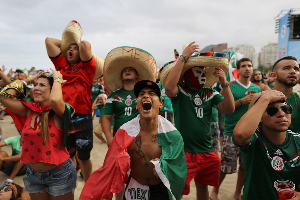 . Mexico soccer fan Jose Reyna, center, reacts as he watches his team\'s World Cup match with Cameroon inside the FIFA Fan fest area on Copacabana beach in Rio de Janeiro, Brazil, Friday, June 13, 2014. Mexico won 1-0. (AP Photo/Leo Correa)
