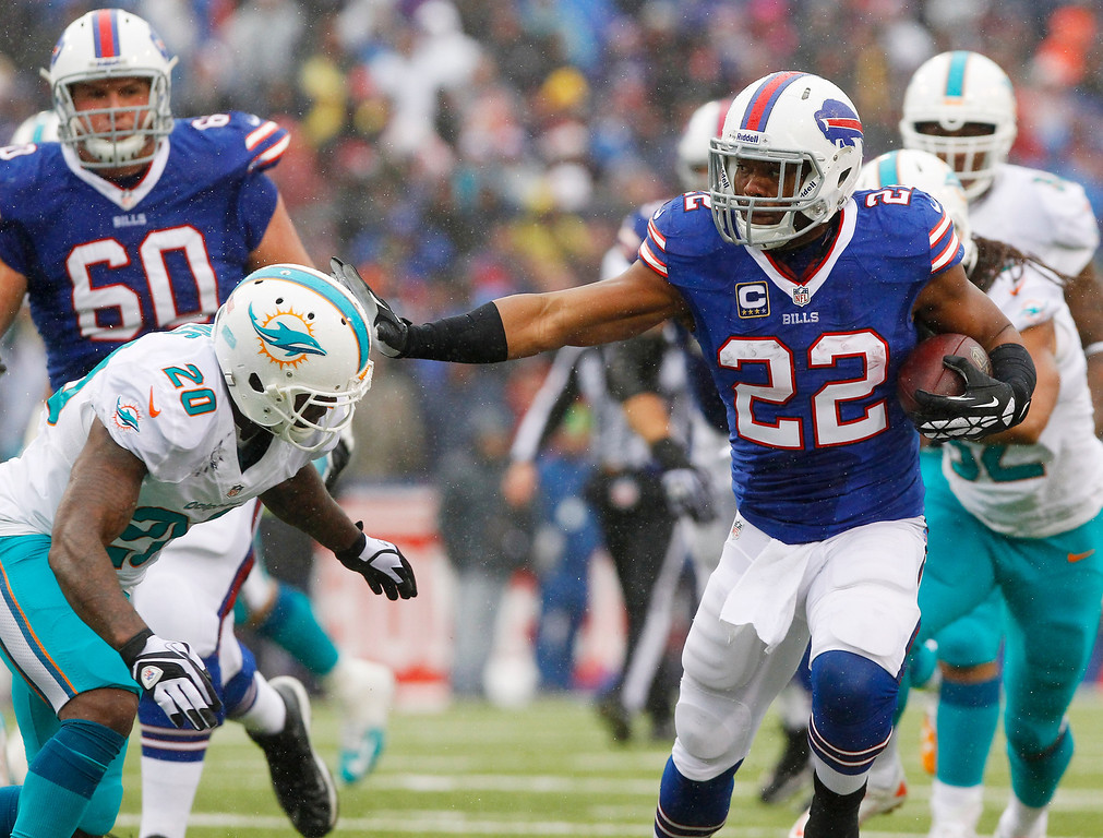 . Buffalo Bills running back Fred Jackson (22) fends off Miami Dolphins free safety Reshad Jones (20) during the first half of an NFL football game Sunday, Dec. 22, 2013, in Orchard Park, N.Y. (AP Photo/Bill Wippert)