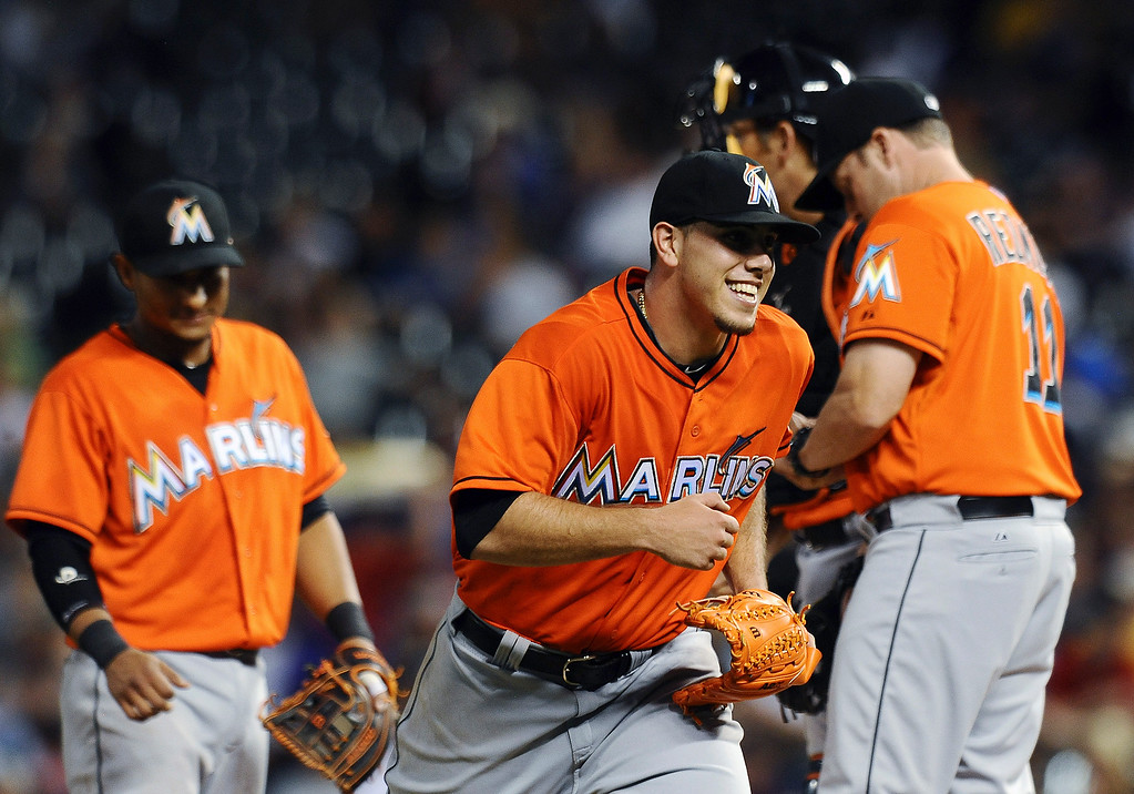 . Miami Marlins starting pitcher Jose Fernandez, center, is all smiles after being pulled from the baseball game with a 4-2 lead in the eighth inning against the Colorado Rockies on Tuesday, July 23, 2013, in Denver. (AP Photo/Chris Schneider)