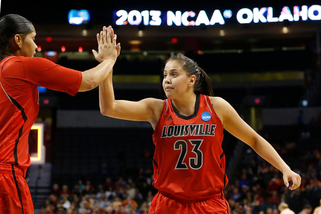 . Louisville forward guard Shoni Schimmel (23) high-fives Monique Reid, left, at the end of the first half of the Oklahoma City regional final in the NCAA women\'s college basketball tournament in Oklahoma City, Tuesday, April 2, 2013.  (AP Photo/Sue Ogrocki)