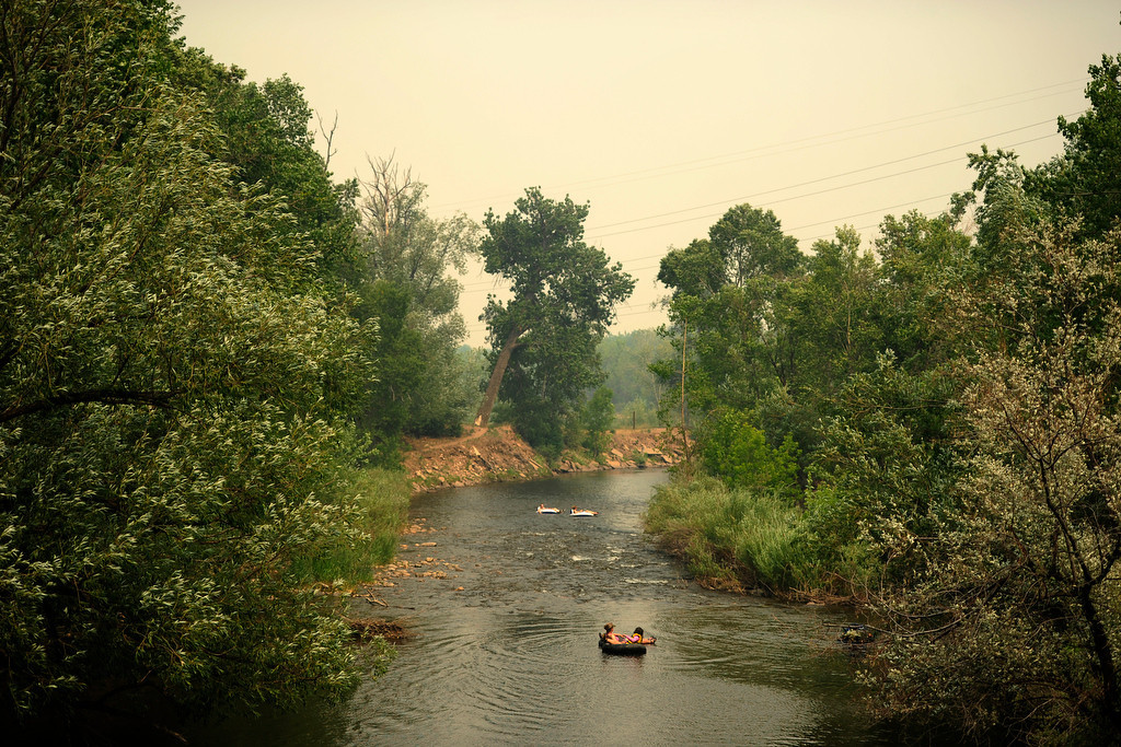 . People float the Poudre River as the High Park fire burns on Sunday, June 17, 2012. High winds caused smoke to blow eastward into Fort Collins and the surrounding area. AAron Ontiveroz, The Denver Post