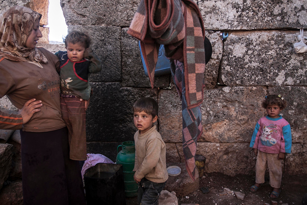 . This Friday, Sept. 27, 2013 photo, shows a displaced Syrian family near Kafer Rouma, amid ancient ruins used as temporary shelter by those families who have fled from the heavy fighting and shelling in the Idlib province countryside of Syria.(AP Photo)