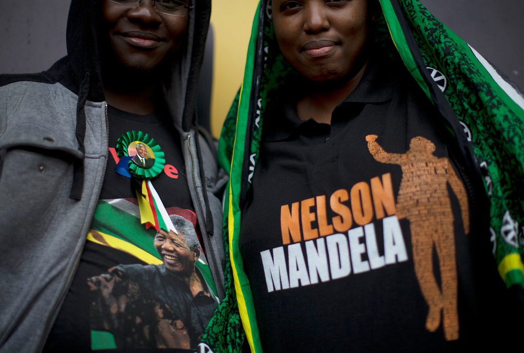 . Mourners display their Nelson Mandela t-shirts as they wait for the memorial service for former South African president Nelson Mandela at the FNB Stadium in Soweto near Johannesburg, Tuesday, Dec. 10, 2013. (AP Photo/Muhammed Muheisen)