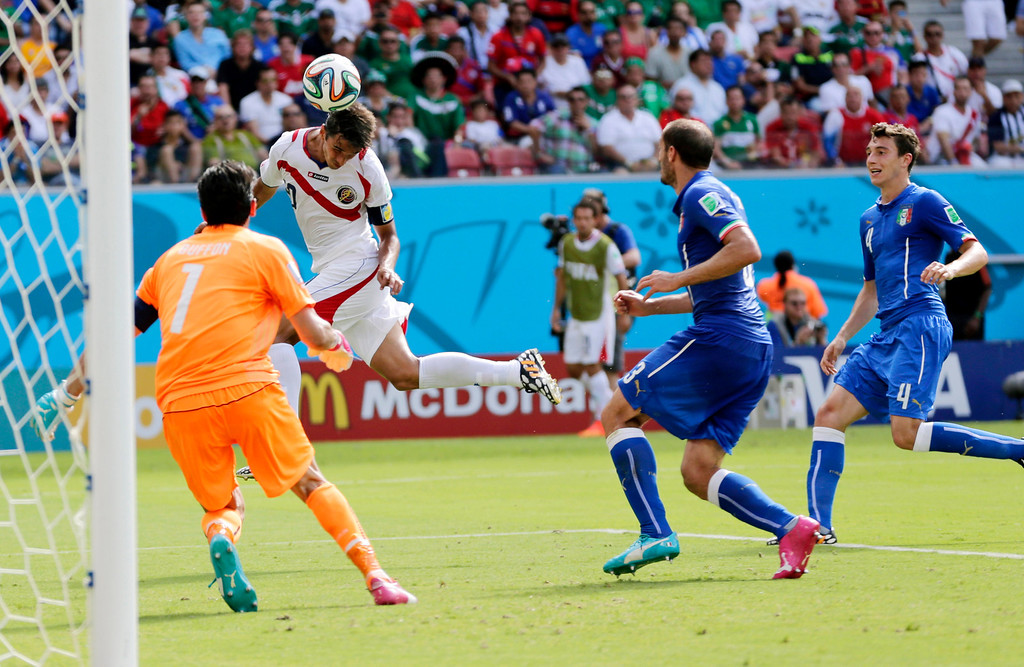 . Costa Rica\'s Bryan Ruiz heads the ball to score his side\'s first goal over Italy\'s goalkeeper Gianluigi Buffon during the group D World Cup soccer match between Italy and Costa Rica at the Arena Pernambuco in Recife, Brazil, Friday, June 20, 2014.(AP Photo/Petr David Josek)