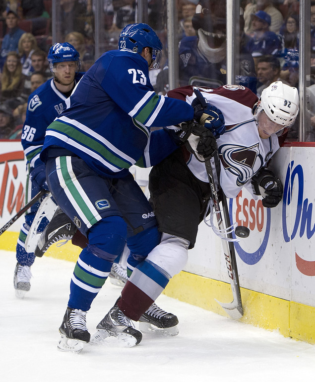 . Alexander Edler #23 of the Vancouver Canucks checks Gabriel Landeskog #92 of the Colorado Avalanche as they battle for the puck during the third period in NHL action on March 28, 2013 at Rogers Arena in Vancouver, British Columbia, Canada.  (Photo by Rich Lam/Getty Images)