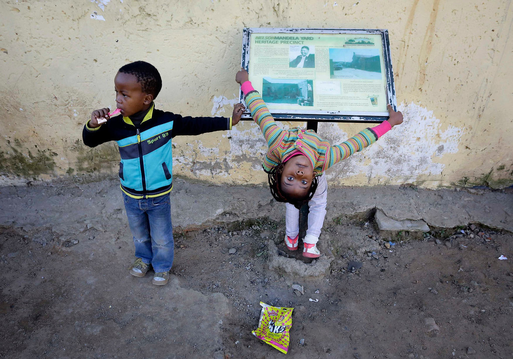 . Children play by an information board at a house former President Nelson Mandela stayed in during the 1940s, in Johannesburg\'s Alexandra township June 25, 2013. Mandela remained in a critical condition in hospital on Tuesday after being admitted more than two weeks ago with a lung infection, the government said.   REUTERS/Kevin Coombs