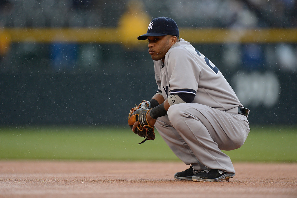 . Robinson Cano (24) of the New York Yankees squats in the infield as a light rain comes down during their game against the Colorado Rockies May 9, 2013 at Coors Field. (Photo By John Leyba/The Denver Post)