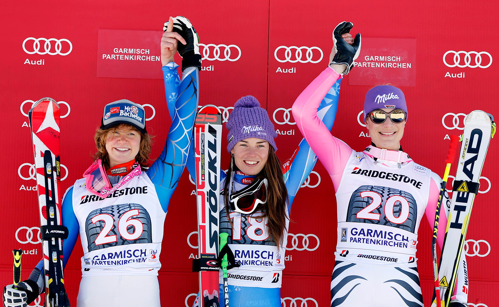 . From left, second placed Laurenne Ross, of the United States, first placed Slovenia\'s Tina Maze and third placed Germany\'s Maria Hoefl Riesch celebrate on the podium of an alpine ski, women\'s World Cup downhill, in Garmisch-Partenkirchen, Germany, Saturday, March 2, 2013. (AP Photo/Marco Trovati)