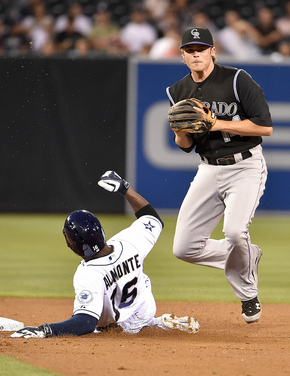. SAN DIEGO, CA - AUGUST 12:  Josh Rutledge #14 of the Colorado Rockies throws over Abraham Almonte #16 of the San Diego Padres as he turns a double play during the second inning of a baseball game at Petco Park August, 12, 2014 in San Diego, California.  (Photo by Denis Poroy/Getty Images)