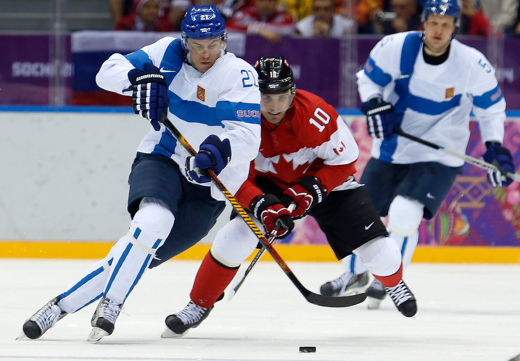 . Finland forward Jori Lehtera chases down the puck against Canada forward Patrick Sharp in the second period of a men\'s ice hockey game at the 2014 Winter Olympics, Sunday, Feb. 16, 2014, in Sochi, Russia. (AP Photo/Mark Humphrey)