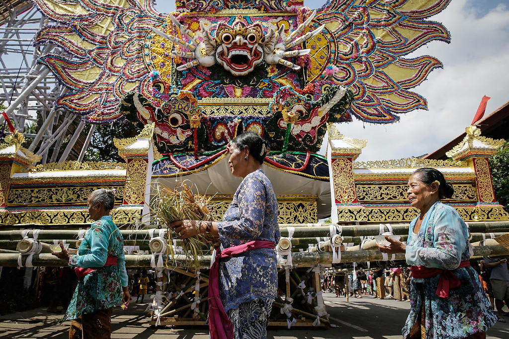 """. Balinese women walk along the \""""Bade\"""" (body carrying tower) as they prepare the Royal cremation ceremony on November 1, 2013 in Ubud, Bali, Indonesia. (Photo by Agung Parameswara/Getty Images)"""