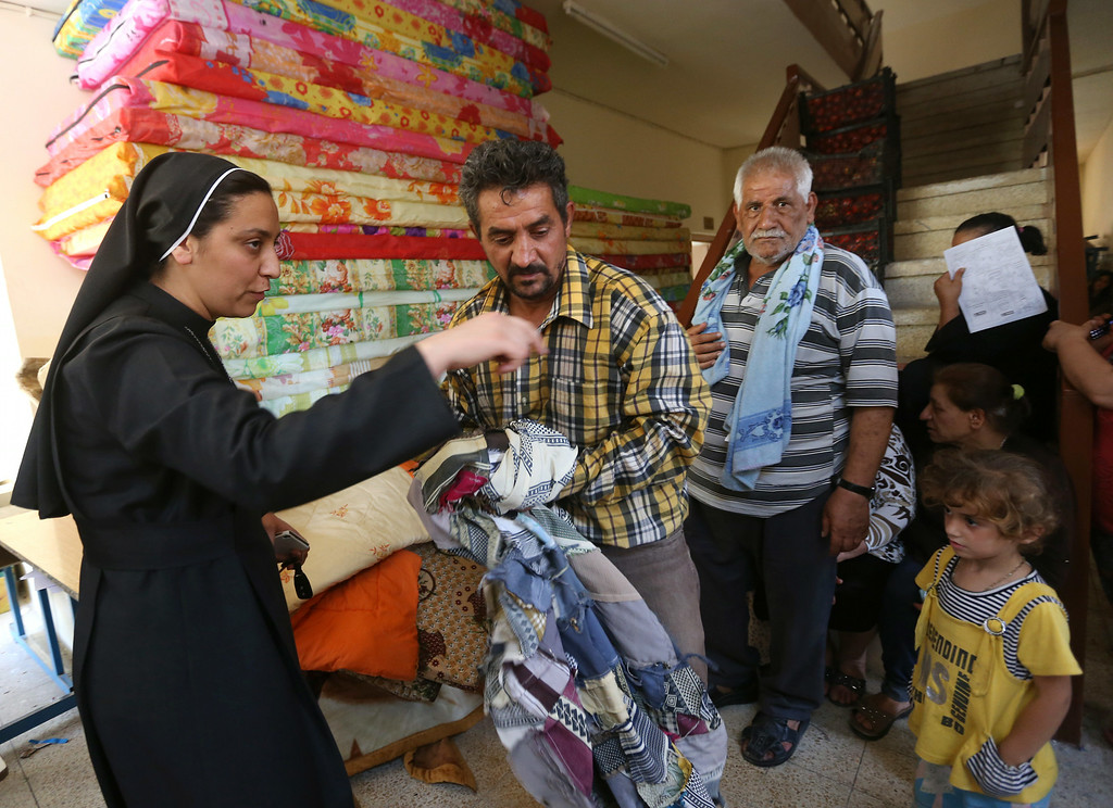 . An Iraqi nun, left, speaks with a Christian man who fled with his family from Christian villages near Mosul province in Iraq, at a school which turned as a shelter for the displaced Christian families, in Ainkawa, a suburb of Irbil, with a majority Christian population, Iraq, Friday, June 27, 2014. Around 2,000 Christians had entered the Kurdish city of Irbil by Thursday morning, June 26. A Christian official there said the Kurdish region is the only part of Iraq where Christians are protected from violence. (AP Photo/Hussein Malla)