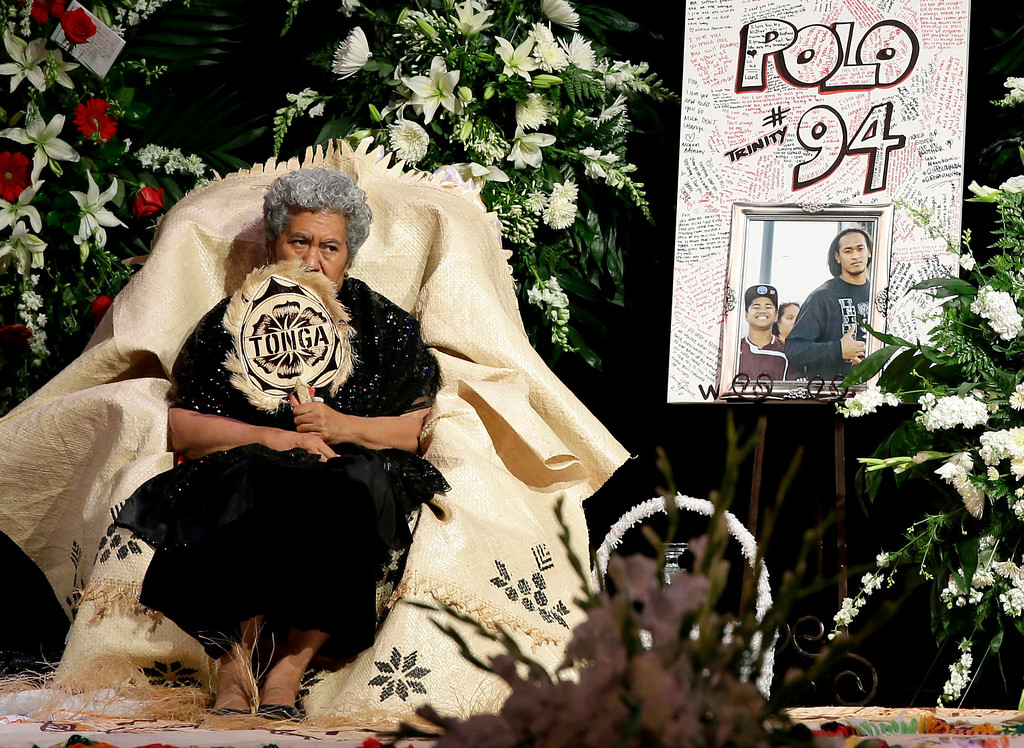 """. Sinai Falemaka, the family matriarch, fans herself as she sits on stage by the remains of Texas A&M redshirt freshman Polo Manukainiu and Andrew \""""Lolo\"""" Uhatafe during a memorial service at Trinity High School, Friday, Aug. 9, 2013, in Euless, Texas. Manukainiu,19, and Uhatafe, 13, were killed in a single car accident in Northern New Mexico, on July 29. Also killed was 18-year-old Utah recruit Gaius \""""Keio\"""" Vaenuku. (AP Photo/Tony Gutierrez)"""
