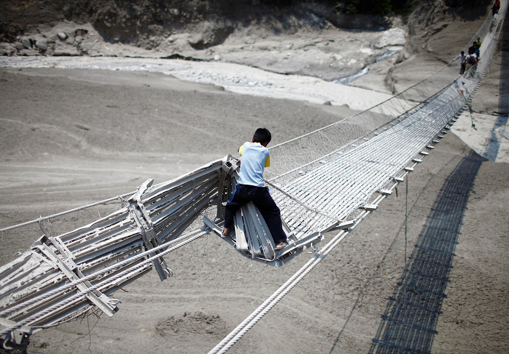 . A boy tries to cross a damaged suspension bridge, after a flash flood caused by an avalanche in the Annapurna mountain range on Saturday, in Kaski district May 6, 2012. At least 17 people, including three foreigners, are confirmed to have died during the flood in Pokhara and adjoining villages in Kaski district, according to Police inspector Ravindra Nath Poudel of Kaski District. REUTERS/Navesh Chitrakar