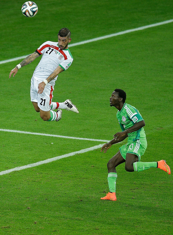 . Iran\'s Ashkan Dejagah heads a ball as Nigeria\'s Juwon Oshaniwa, right, looks on during the group F World Cup soccer match between Iran and Nigeria at the Arena da Baixada in Curitiba, Brazil, Monday, June 16, 2014. The match ended in a goalless draw.(AP Photo/Michael Sohn)