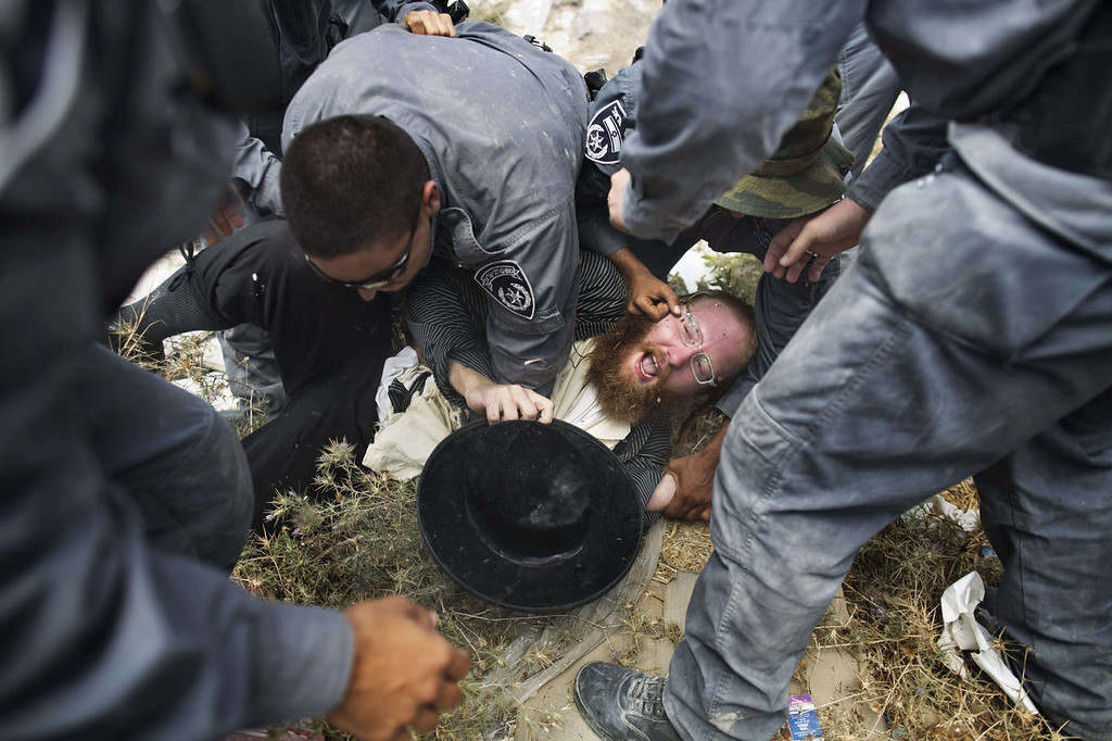 . An Ultra-Orthodox Jewish man is arrested by Israeli police in Ramat Beit Shemesh West of Jerusalem on August 12 2013, after dozens of Haredim protest against desecration of ancient graves were discovered at a new housing construction site. Some 14 Ultra-orthodox Jews were arrested.   MENAHEM KAHANA/AFP/Getty Images