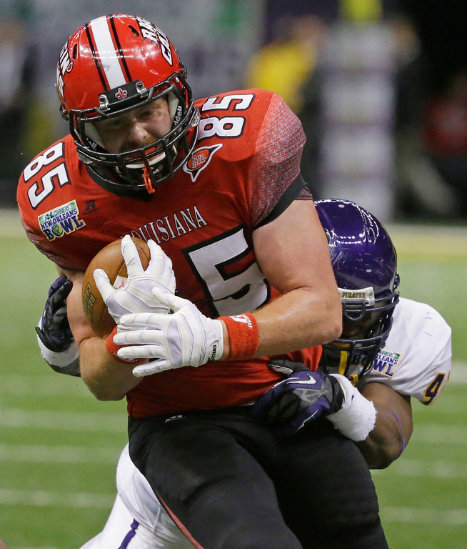 . Louisiana-Lafayette tight end Ian Thompson (85) is taken down by East Carolina linebacker Gabriel Woullard (42) in the first half of the New Orleans Bowl, an NCAA college football game in New Orleans, Saturday, Dec. 22, 2012. (AP Photo/Bill Haber)