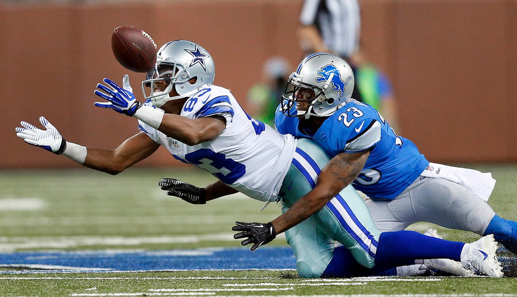 . Dallas Cowboys wide receiver Terrance Williams (83) reaches for a pass as Detroit Lions cornerback Chris Houston (23) defends in the second half of an NFL football game in Detroit, Sunday, Oct. 27, 2013. (AP Photo/Rick Osentoski)