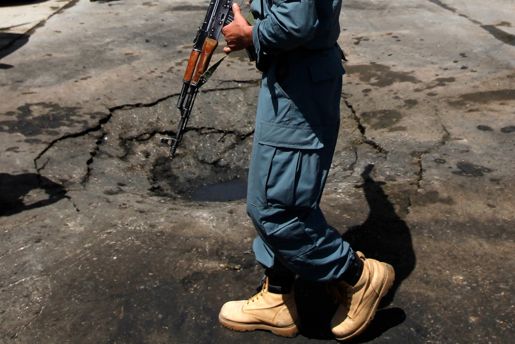 . An Afghan policeman stands guard at the site of a suicide attack in Kabul May 16, 2013. REUTERS/Mohammad Ismail