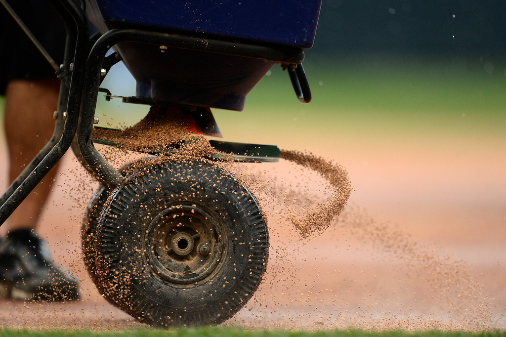 . Groundskeepers   throw down a premium field conditioner to dry out the wet spots on the infield during the Colorado Rockies New York Yankees game May 9, 2013 at Coors Field. (Photo By John Leyba/The Denver Post)