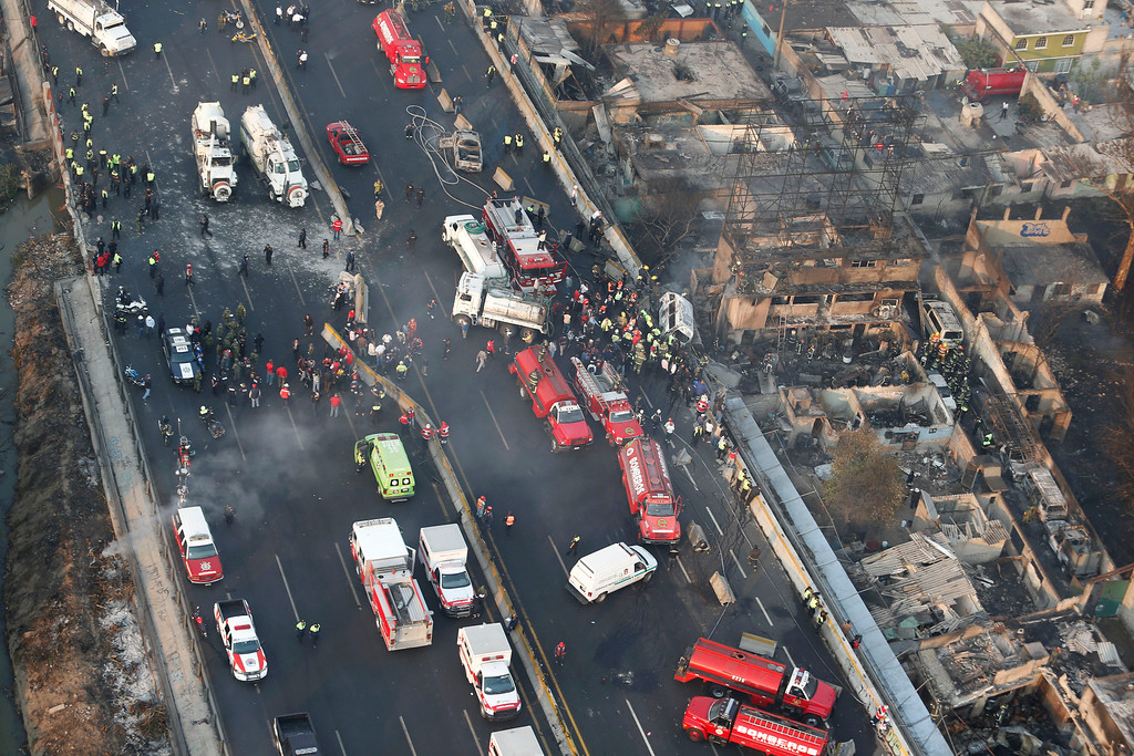 . Aerial view shows first responders working next to destroyed homes and vehicles after a gas tanker truck exploded on a highway in the Mexico City suburb of Ecatepec early Tuesday, May 7, 2013.  The blast killed and injured dozens, according to the Citizen Safety Department of Mexico State. Officials did not rule out the possibility the death toll could rise as emergency workers continued sifting through the charred remains of vehicles and homes built near the highway on the northern edge of the metropolis. (AP Photo)