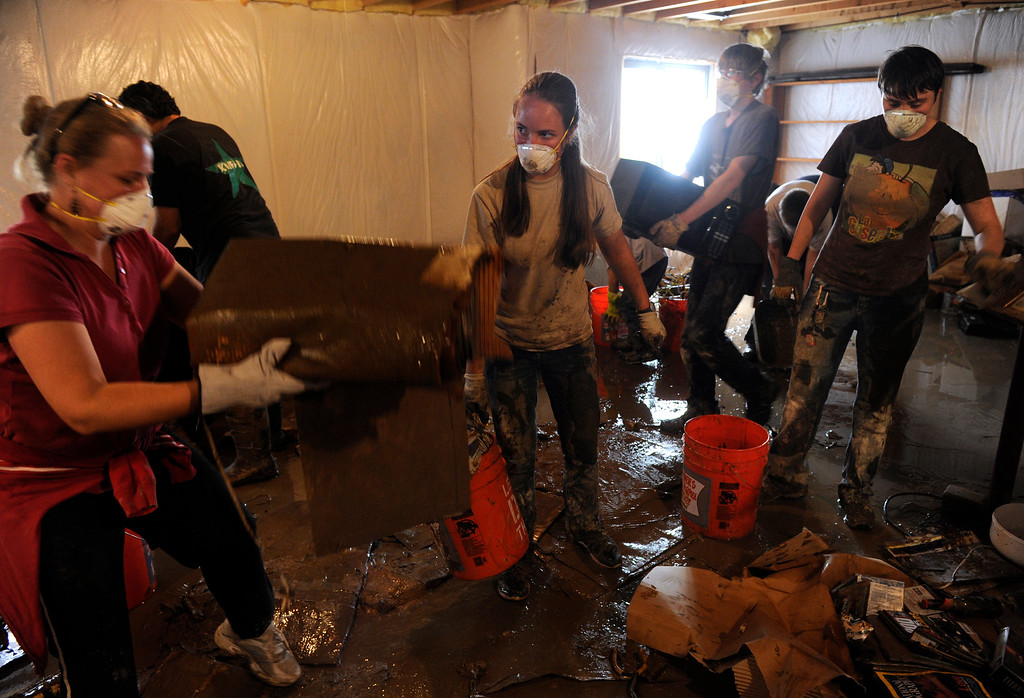 . LONGMONT, CO - Sept. 20: Members of Grace Church wade through several inches of mud and sludge in the basement of Maryellen Boop who says she lost almost everything from that room. Residents along Wade Rd. just south of the Twin Peaks Golf Course continue the cleanup after floods last week devastated the neighborhood. (Photo By Kathryn Scott Osler/The Denver Post)