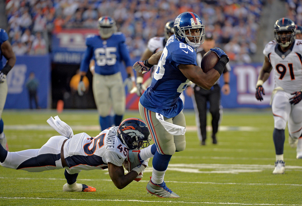 . Denver Broncos cornerback Dominique Rodgers-Cromartie (45) grabs ahold of New York Giants wide receiver Hakeem Nicks (88) by the foot to bring him down after a gain during the third quarter September 15, 2013 MetLife Stadium. (Photo by John Leyba/The Denver Post)