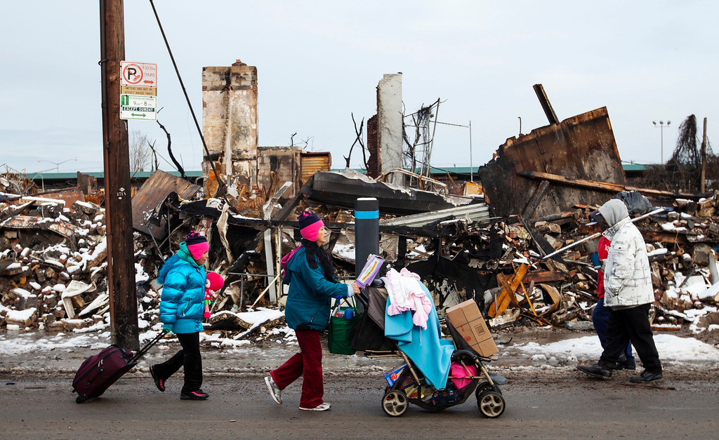 . People push carts with donated items in them past buildings destroyed by a fire that took place during hurricane Sandy and through snow left on the ground after a nor\'easter, also known as a northeaster storm, in the Queens borough neighborhood of Rockaway Park, New York, November 8, 2012. REUTERS/Lucas Jackson