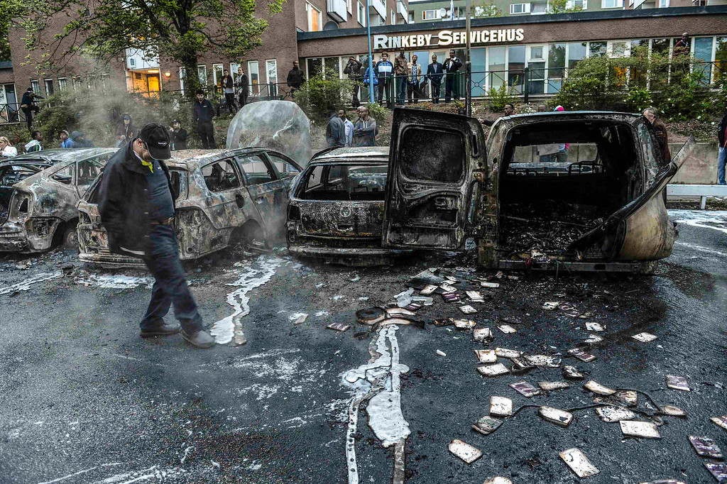 . A bystander checks the debris around a row of burnt cars in the suburb of Rinkeby after youths rioted in several different suburbs around Stockholm May 23, 2013. Hundreds of youth have torched cars and attacked police in four nights of riots in immigrant suburbs of Sweden\'s capital, shocking a country that dodged the worst of the financial crisis but failed to solve youth unemployment and resentment among asylum seekers.  REUTERS/Fredrik Sandberg/Scanpix