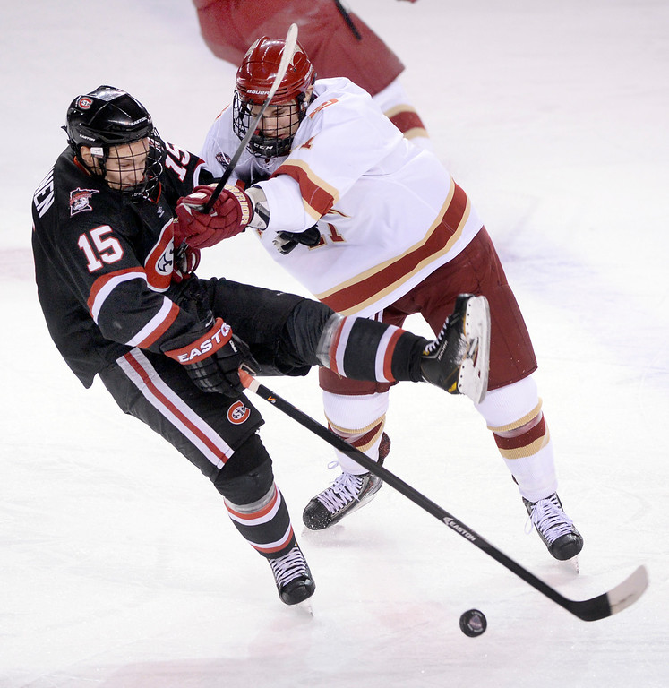 . DENVER, CO. - JANUARY 10: Denver defenseman Nolan Zajac (11) took St. Cloud State freshman Niklas Nevalainen (15) off the puck in the first period. The University of Denver hockey team hosted St. Cloud State at Magness Arena Friday night, January 10, 2014. Photo By Karl Gehring/The Denver Post